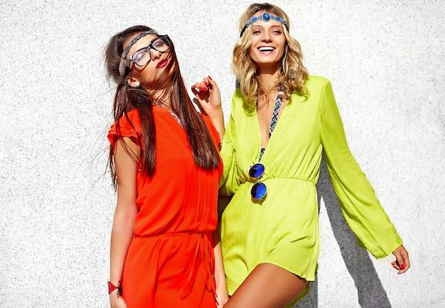 Retrato da moda de dois modelos de mulheres jovens hippie em dia ensolarado de verão em roupas brilhantes coloridas hipster