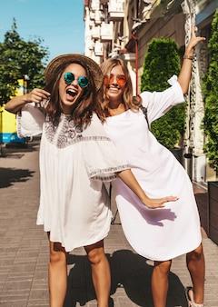 Retrato da moda de dois modelos de mulheres jovens loiras e morenas hippie elegante em dia ensolarado de verão em roupas brancas hipster posando