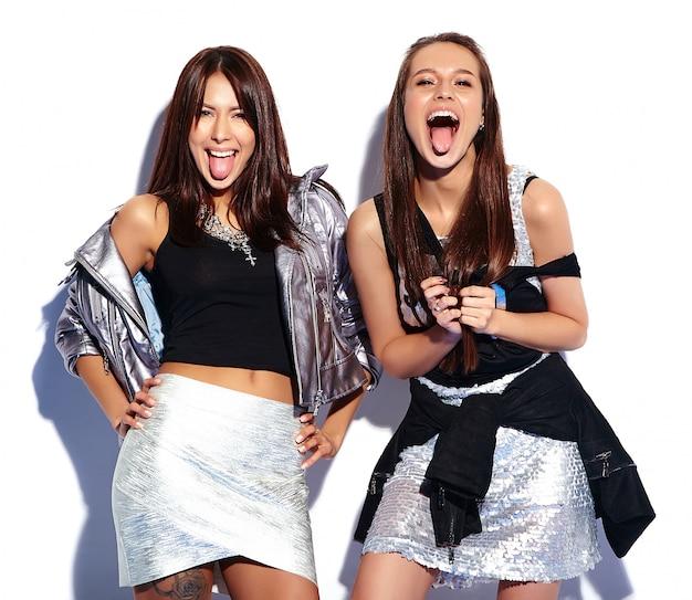 Retrato da moda de dois modelos morenas sorridentes em roupas de verão casual hipster isoladas no branco