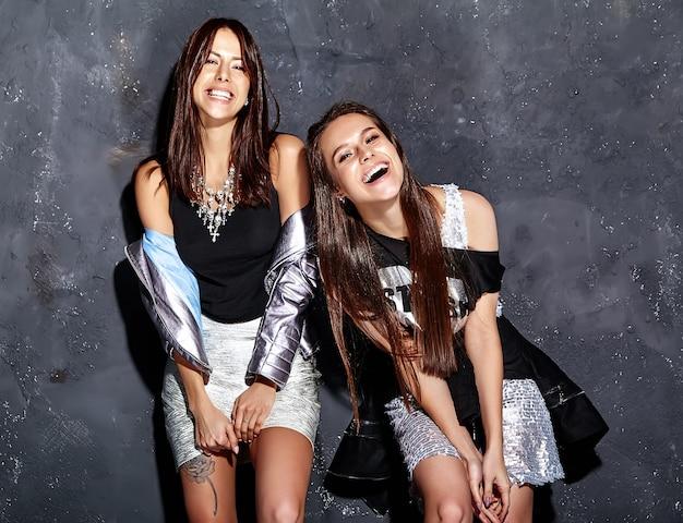 Retrato da moda de dois modelos morenas sorridentes em roupas de verão casual hipster preto posando perto de parede cinza escuro
