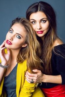 Retrato da moda de duas incríveis mulheres loiras e morenas, usando maquiagem esfumada brilhante e elegantes roupas casuais inteligentes.