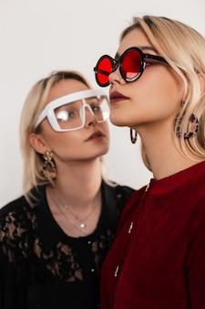 Retrato da moda de duas lindas meninas com elegantes óculos escuros em roupas vintage com vestidos