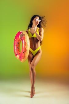 Retrato da moda de jovem apto e esportivo com donut de borracha em um elegante maiô amarelo na parede gradiente, corpo perfeito pronto para o verão