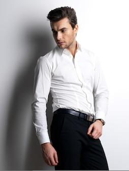 Retrato da moda de jovem com camisa branca posa na parede com sombras contrastantes