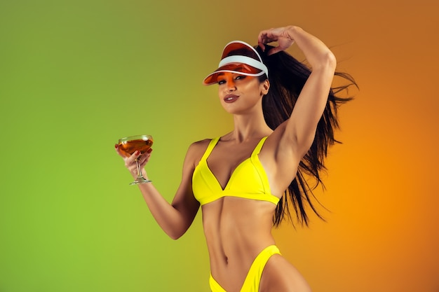Retrato da moda de jovem em forma e mulher esportiva com coquetel em um elegante maiô de luxo amarelo na parede gradiente, corpo perfeito pronto para o verão