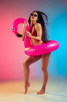 Retrato da moda de jovem em forma e mulher esportiva com flamingo de borracha em um elegante maiô vermelho na parede gradiente, corpo perfeito pronto para o verão