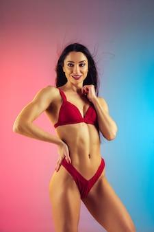 Retrato da moda de jovem em forma e mulher esportiva em um elegante maiô de luxo vermelho na parede gradiente, corpo perfeito pronto para o verão