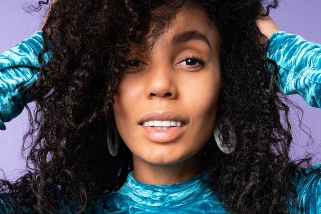 Retrato da moda de linda mulher brasileira com cabelos cacheados em elegante vestido de veludo