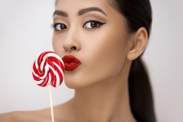 Retrato da moda de mulher asiática com pirulito em estúdio