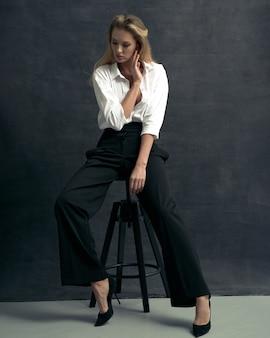 Retrato da moda de mulher bonita com camisa branca e calça preta em estúdio de fundo escuro