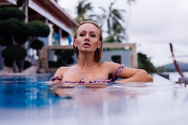 Retrato da moda de mulher caucasiana de biquíni na piscina azul de férias em coudy day natural light
