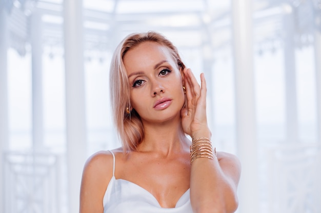 Retrato da moda de mulher loira europeia em vestido romântico de verão branco de seda com pulseira dourada e brincos