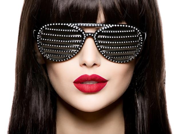 Retrato da moda de mulher usando óculos escuros pretos com diamantes e lábios vermelhos