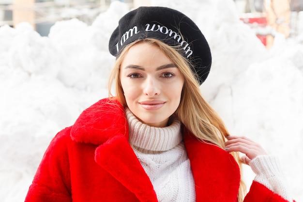 Retrato da moda de uma bela jovem caminha pela cidade sorrindo, casaco de pele vermelha