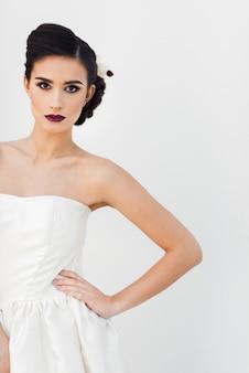 Retrato da moda de uma jovem garota em um vestido branco e flores no cabelo dela