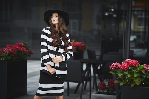 Retrato da moda de uma jovem modelo com maquiagem da moda, usando um chapéu da moda e vestido posando ao ar livre em um dia de verão