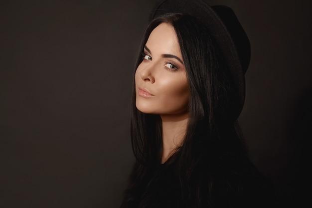 Retrato da moda de uma jovem mulher bonita com maquiagem suave e cabelo preto perfeito em um bl ...