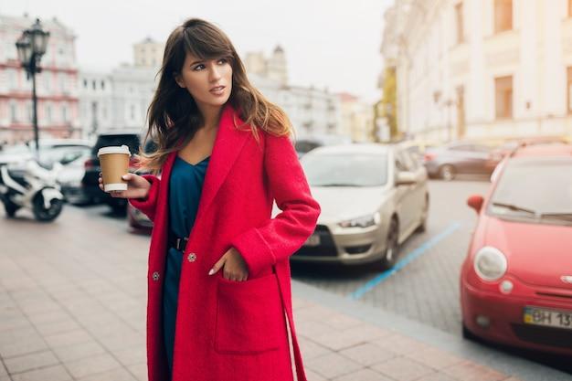 Retrato da moda de uma jovem mulher bonita e elegante caminhando na rua da cidade com um casaco vermelho, tendência do estilo outono, bebendo café, sorrindo, feliz, usando um vestido de seda azul