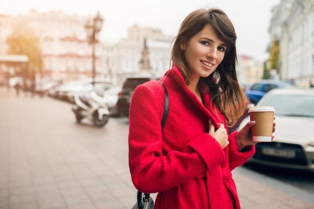 Retrato da moda de uma jovem mulher bonita e elegante caminhando na rua da cidade com um casaco vermelho, tendência do estilo outono, bebendo café, sorrindo, feliz