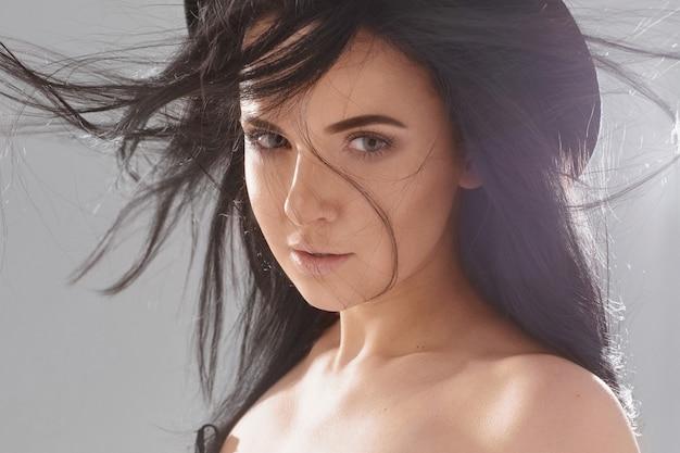 Retrato da moda de uma jovem mulher com maquiagem nude e cabelos esvoaçantes, usando um chapéu preto da moda