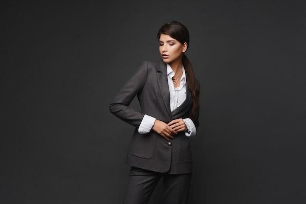 Retrato da moda de uma jovem mulher de negócios em um terno moderno sobre fundo cinza