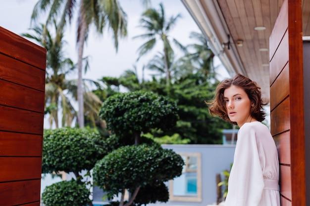 Retrato da moda de uma jovem mulher muito elegante em um vestido branco leve de verão e grandes botas pretas enormes em uma luxuosa villa rica