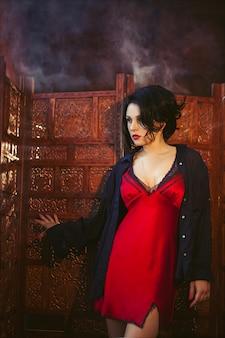 Retrato da moda de uma linda jovem morena em lingerie vermelha e uma camisa preta em um interior escuro