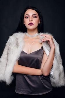 Retrato da moda de uma linda menina morena em pele com acessórios de luxo. modelo de beleza com joias em fundo preto. menina com casaco de pele de vison branco. mulher bonita do inverno de luxo.