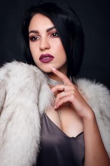 Retrato da moda de uma linda menina morena em pele com acessórios de luxo