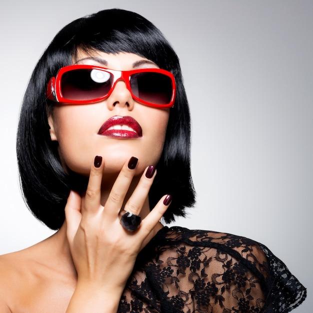 Retrato da moda de uma linda mulher morena com foto de cabelo curto e unhas de beleza