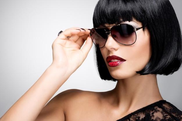 Retrato da moda de uma linda mulher morena com penteado baleado e óculos de sol vermelhos