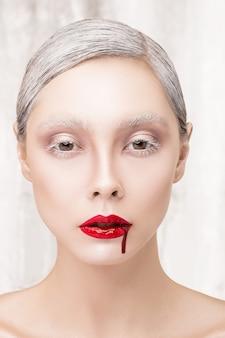 Retrato da moda de uma menina vampira com sangue. lentes de contato