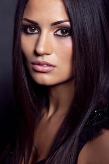 Retrato da moda de uma modelo morena, com cabelos longos e lisos e maquiagem da moda