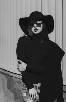 Retrato da moda de uma mulher bonita morena com chapéu da moda e óculos elegantes, posando para as persianas. tonalidade em preto e branco