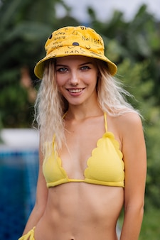 Retrato da moda de uma mulher loira caucasiana de biquíni amarelo e panamá na beira da piscina azul