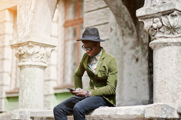 Retrato da moda do homem afro-americano preto na jaqueta de veludo verde e chapéu preto