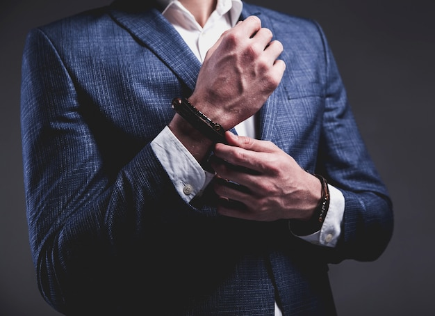 Retrato da moda do homem bonito modelo jovem empresário vestido elegante terno azul na cinza