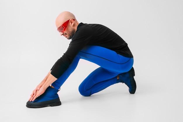 Retrato da moda do homem elegante de meia-calça azul e botas azuis, alongamentos e exercícios.