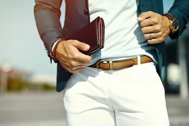 Retrato da moda do homem jovem bonito modelo de empresário em pano casual terno com acessórios nas mãos