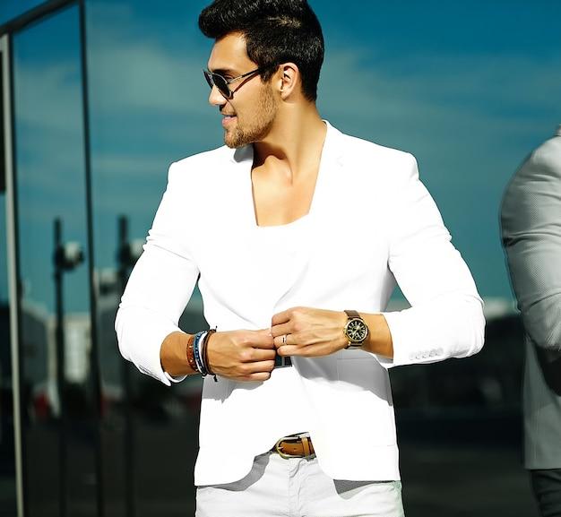 Retrato da moda do homem jovem bonito modelo sexy casual terno branco em óculos de sol em terno branco na rua