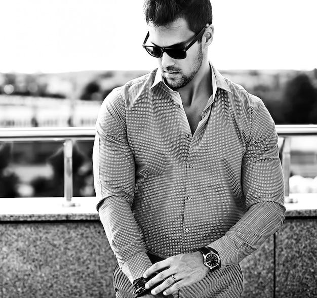 Retrato da moda do homem jovem bonito modelo sexy em roupas casuais em óculos de sol na rua