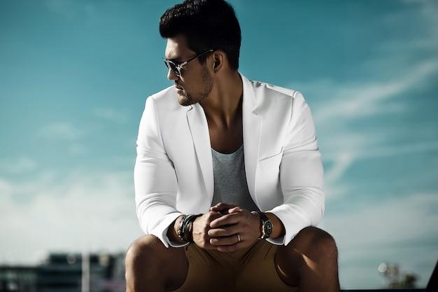 Retrato da moda do homem jovem bonito modelo sexy empresário casual pano terno em óculos de sol sentado na rua atrás do céu azul