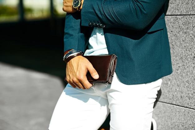 Retrato da moda do homem jovem modelo bonito de empresário em pano casual terno com acessórios nas mãos