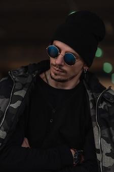 Retrato da moda do modelo de cara bonito hipster com óculos de sol da moda e chapéu preto na jaqueta militar de inverno e pulôver na cidade