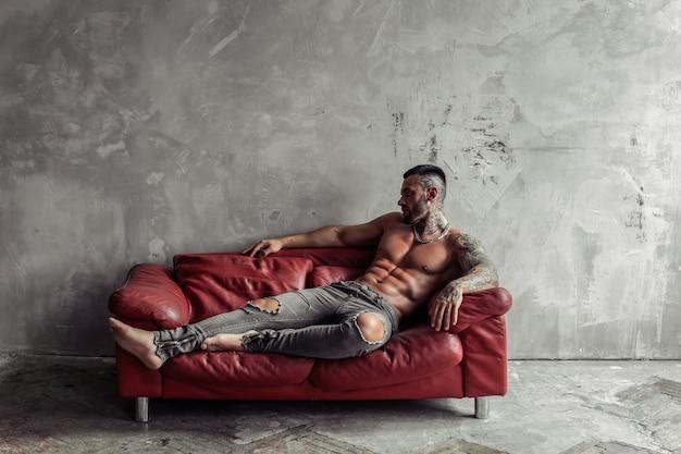 Retrato da moda do modelo masculino nu sexy com tatuagem e barba negra, deitado em pose quente no sofá de couro vermelho. interior de quarto loft com muro de concreto cinza.