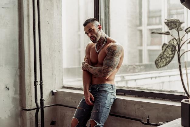 Retrato da moda do modelo masculino nu sexy com tatuagem e uma barba preta em pé em pose quente perto da janela. interior de quarto loft com muro de concreto cinza.