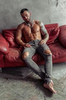 Retrato da moda do modelo masculino nu sexy com tatuagem e uma barba preta, sentado em pose quente no sofá de couro vermelho. interior de quarto loft com muro de concreto cinza.