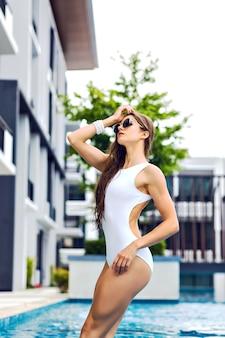 Retrato da moda do verão de uma mulher morena com cabelos longos incríveis se passando perto da piscina