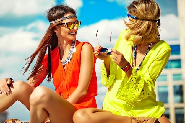 Retrato da moda dos modelos de mulheres jovens hippie em dia ensolarado de verão em roupas hippie coloridas brilhantes