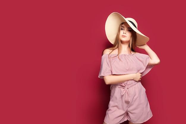 Retrato da moda e beleza de uma jovem linda em um vestido vermelho claro e um chapéu de palha em uma parede vermelha